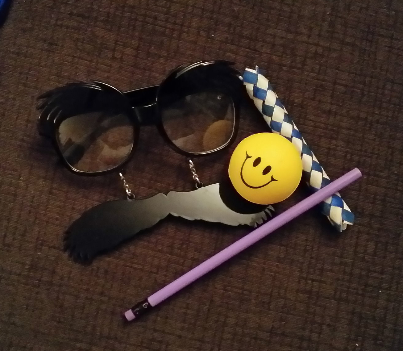 "Photo of a pair of ""Groucho"" glasses, a smiley face stress ball, a pencil, and a woven finger trap."